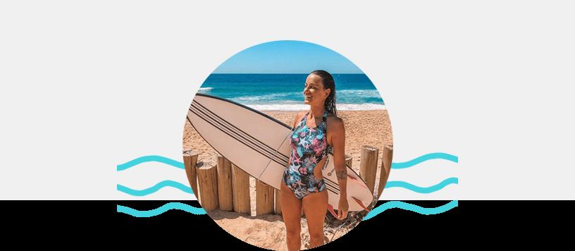 Na imagem a Barbara Speck aparece com os cabelos molhados em uma praia com o mar ao fundo, seguirando uma prancha de surf e vestindo um maio florido da Loveboard