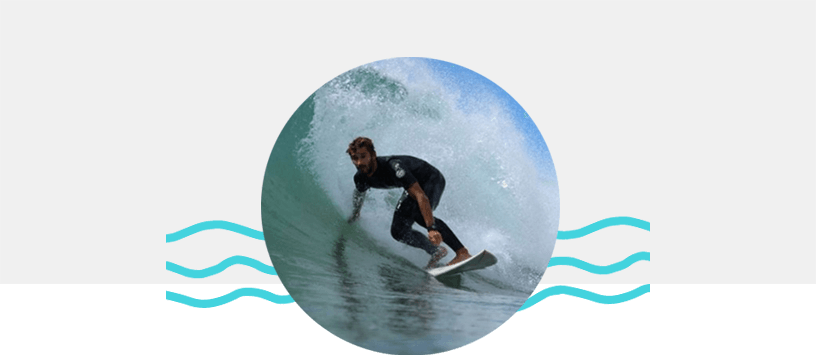 Na imagem o João Budny aparece com sufando uma onda, usando um long john em cima de uma prancha