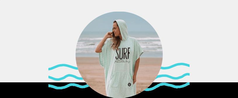 Na imagem a Lisi está na praia posando com um poncho de surf verde claro, com os cabelos loiros soltos.