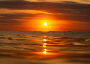 Nascer do sol e um belo céu laranja em fotografia aquática