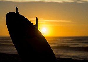 Belo pôr do sol dourado com prancha de surf e o mar