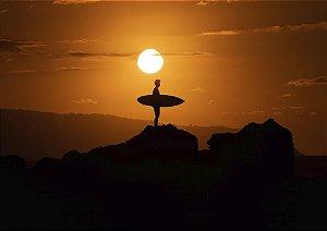 Surfista com sua prancha em cima de uma pedra no pôr do sol
