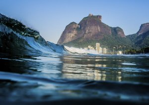 Fotografia aquática de onda e alguns prédios e monte ao fundo