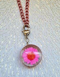 Colar de corrente rosa e pingente de vidro com flor rosa.