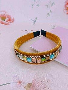 Arco veludo mostarda com pedrinhas coloridas e correntes fina dourada