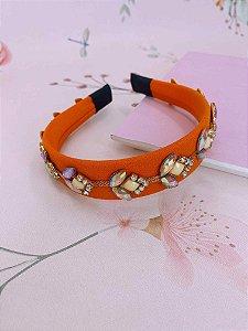 Arco tecido laranja com detalhes em pedrarias