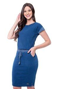Vestido Oriana de malha jeans com recortes listrados, possui elástico no cós, bolsos funcionais e detalhe vazado nas costas.
