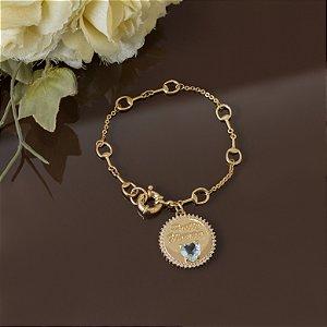 Pulseira dourada com medalha e cristal de coração azul