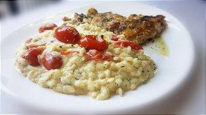 Filé de pescada grelhado ao molho de ervas, servido com risoto de tomate confit