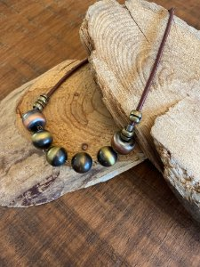 Colar curto de fio de seda ,esferas em polímero e detalhes de metal banhado.