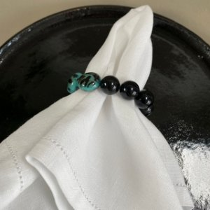 Kit com 4 porta guardanapos com esferas em polímero preto e rajado.