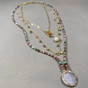Conjunto de colares com cristais multicoloridos e correntes douradas.