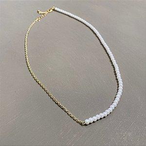 Colar curto com pérolas em polímero e corrente dourada.