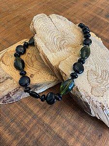 Colar curto de peças em polímero preto e verde translúcidos e entremeios de cristais tchecos lapidados.