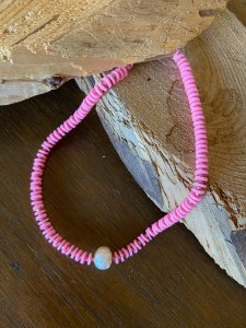 Colar gargantilha com borrachinhas indianas rosa chiclete, com detalhes de metal banhado e pérola barroca ao centro.