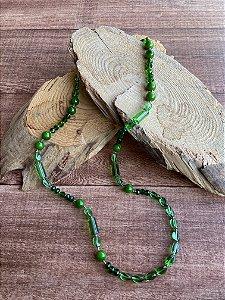 Colar longo de esferas de diversos tamanhos em tons de verde translúcido em polímero.