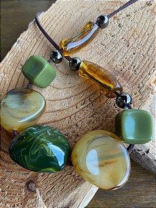 Colar curto com esferas irregulares em tons de verde e cru, fio marrom e detalhes com metal banhado.