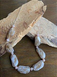 Colar curto com cordão e peças em polímero bege.