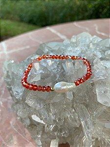 Pulseira de cristais tchecos lapidados translúcidos cor coral,pérola barroca ao centro e detalhes de metal banhado.