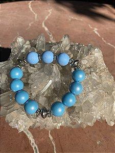 Pulseira de esferas em polímero azul celeste e detalhes de metal banhado.