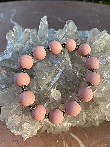 Pulseira de esferas em polímero rosè fosco e detalhes em metal banhado.