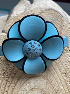 Fivela presilha acetado de flor turquesa e detalhes de zircônias.