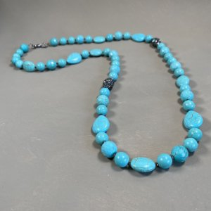 Colar longo de pedras turquesa, entremeios de cristais tchecos lapidados e peças com micro zircônias negras cravejadas.