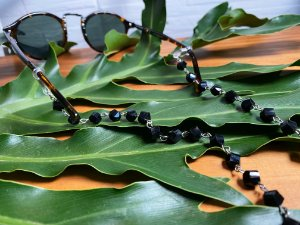 Acessório para óculos alfinetado de cristais lapidados preto.