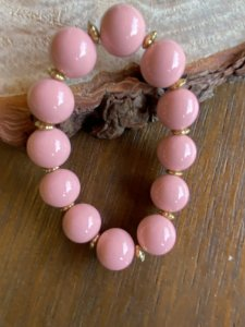 Pulseira de esferas em polímero rosa esmaltado e entremeios de metal banhado.