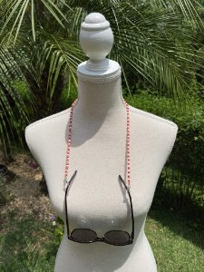 Acessório para óculos e máscara de miçangas vermelha e branca.