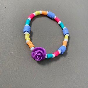 Pulseira de borrachinhas indianas multicores, entremeios de miçangas e flor em polímero lilás ao centro.