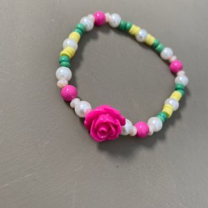 Pulseira mista de pérolas, miçangas, borrachinhas indianas e flor rosa em polímero ao centro.