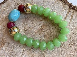 Pulseira de cristais lapidados verde ,esferas de pedra lapidada jade rubi , detalhes de metal banhado e peça em polímero ao centro.