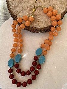 Colar curto duplo de peças em polímero vermelho e laranja, pedra turquesa e entremeios de metal banhado.