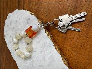 Chaveiro com esferas em polímero cru, entremeios de metal banhado e peça em polímero laranja.