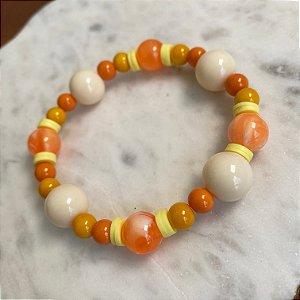Pulseira com esferas em polímero laranja e bege, e borrachinhas indianas amarela.