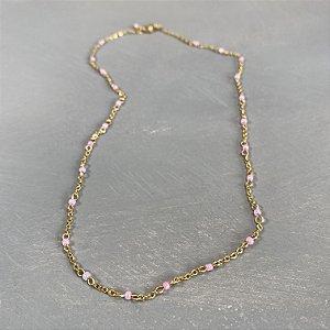 Colar gargantilha de corrente em metal banhado dourado, alfinetado com miçangas rosa claro.