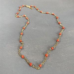 Colar curto de corrente em metal banhado dourado, alfinetado com miçangas laranja.