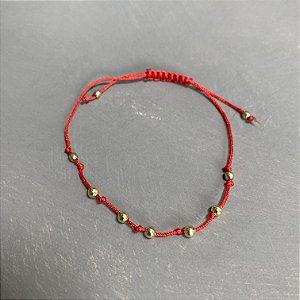 Pulseira com fecho regulável macramê fio vermelho e esferas em metal banhado.