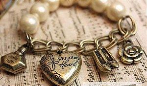 Pulseira dourada com pérolas com pingentes diversos