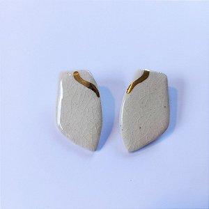 Brinco de cerâmica com detalhe em ouro.