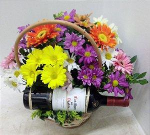 Cesta de flores do campo com garrafa de vinho