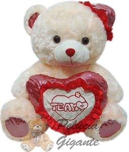 Urso gigante com coração e chapéu vermelho.