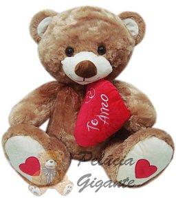 Urso marrom grande com um lindo coração escrito te amo.