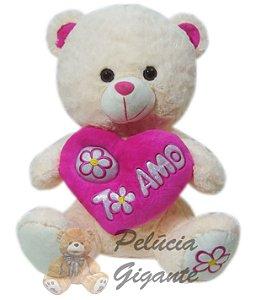 Urso com coração em arco e dois corações escrito te amo.