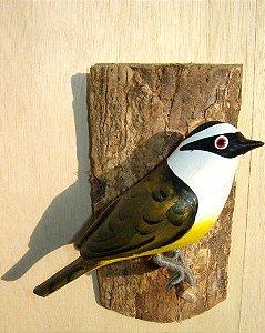 Bem Te Vi  - Pássaro esculpido em madeira apoiado em um puleiro de casca de árvore