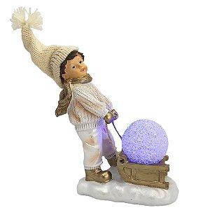 Menino com trenó e bola de Neve