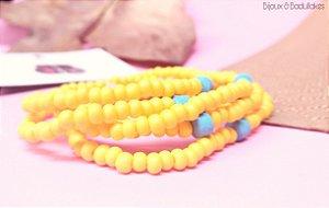 Mix de pulseiras amarelas com cerâmica turquesa.
