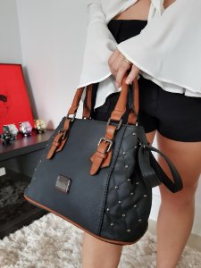 Bolsa preta com detalhes em metal nas laterais e alça caramelo