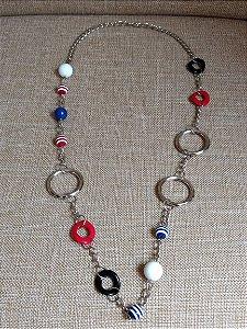 Colar em corrente com argolas de metal, miçangas em formato de bola branca, azul e vermelha listrada de branco e argolas torcidas plásticas preta e vermelha.
